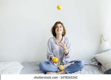 Young female sitting on bed and juggle lemons in white room . Fruit and healthy concepts ideas