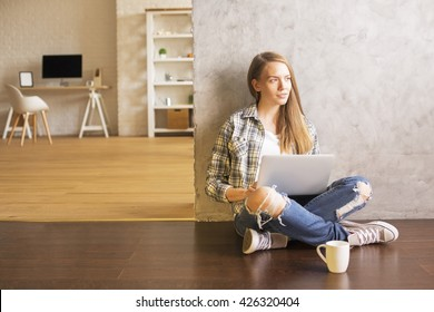 Young female sitting on wooden floor with coffee in interior and using laptop