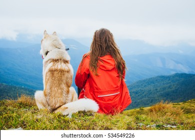 Young female sitting with siberian husky dog in mountains