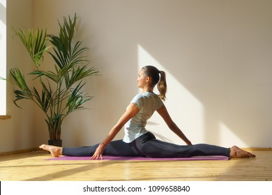 young female sitting in split, stretching training in home interior, natural light