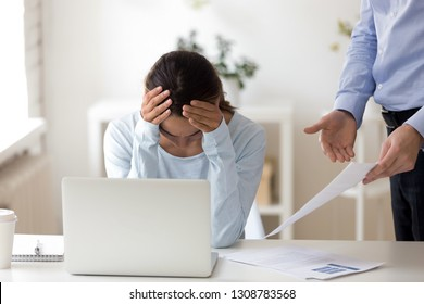 Young female sitting at workplace desk putting her head down, lack working experience employee feels guilty and desperate, company executive manager accusing office worker showing mistakes in report