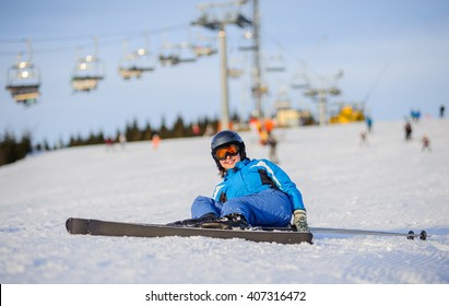 Young female skier in blue ski suit smiling after the fall on mountain slope against ski-lift. Ski resort at Carpathian Mountains. Winter sports concept.