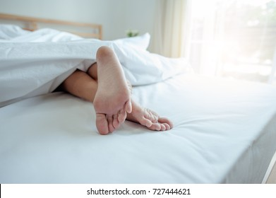 Young female sleeping in bed at home with focus on legs. Feet of woman lying on bed.