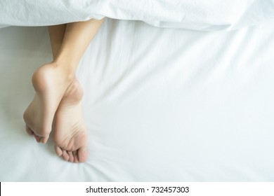 Young female sleeping in bed at home.  Feet under the blanket on her bed on bedroom at background top view.