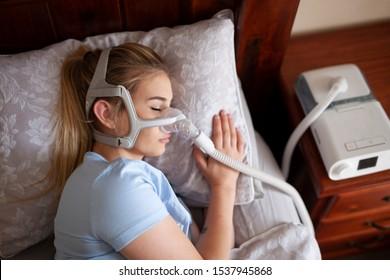 Young female sleeping with cpap machine for sleep apnea