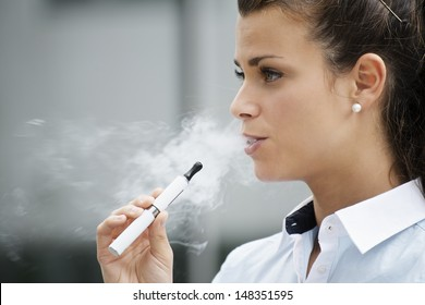 young female smoker smoking e-cigarette outdoors. Head and shoulders, side view
