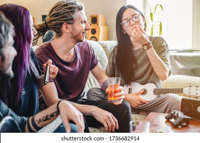 Young female smoking joint with cannabis while playing on music instruments at home with friends