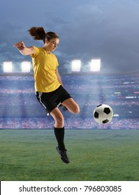 Young female soccer player kicking ball isolated ove white background