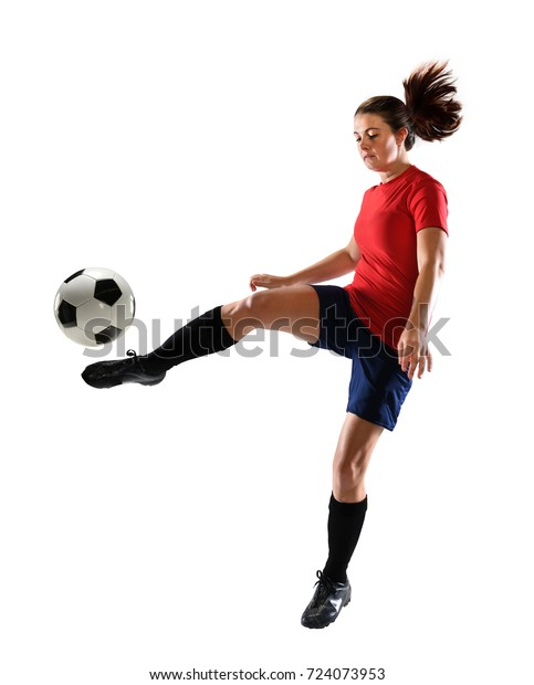 Young female soccer player kicking ball isolated over white background