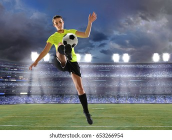 Young female soccer player playing inside  stadium at dusk