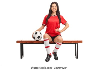 Young female soccer player sitting on a wooden bench and holding a ball isolated on white background