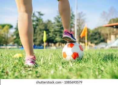 Young female soccer player traning with ball in the stadium - Sporty woman making exercises on the train field - Concept of sportive people lifestyle