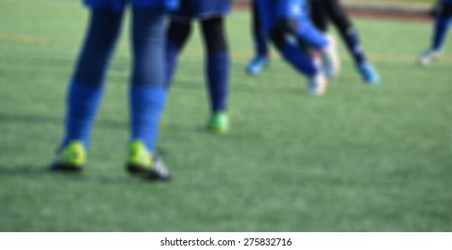 Young female soccer players on turf field - blurred image