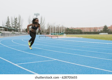 Young female in sportswear running alone on sports ground.