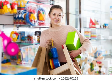 young female standing in the children's store with toys, chair, pack and box