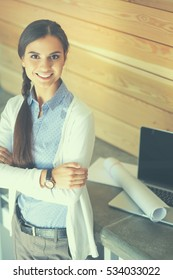 Young female standing near desk with laptop