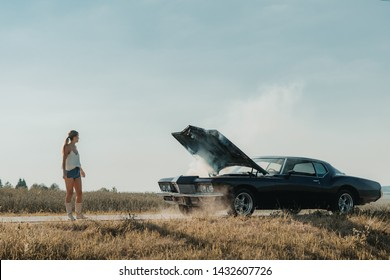 Young female standing near overheated car in the field, bright sunlight, steam under the hood