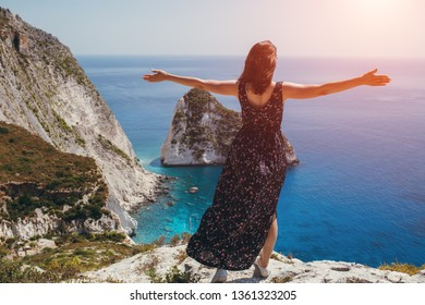 Young female standing on the cliff with arms wide open