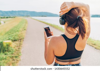 Young female starting jogging and listening to music using smartphone and  wireless headphones.