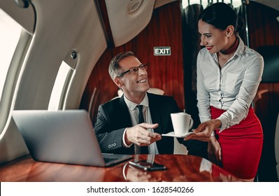 Young female stewardess and senior business man are flying in luxury private jet.