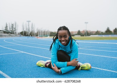 Young female stretching body while sitting on race track of sports ground.