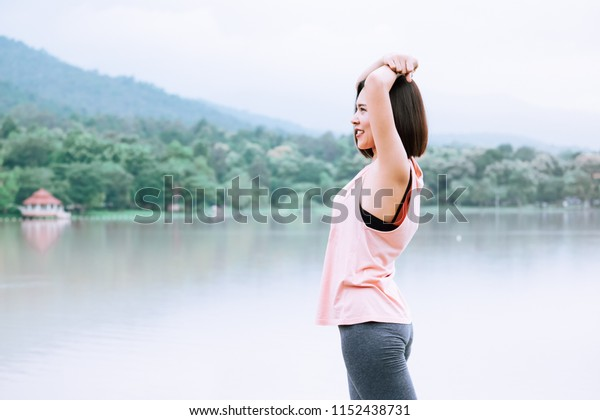 Young female stretching exercise workout before fitness training session at the park. Healthy young woman warming up in morning at the park.