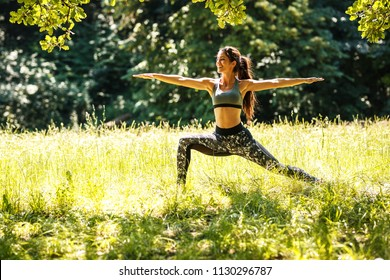 Young female stretching and relaxing after jogging outdoor.She contemplate in yoga warrior pose.