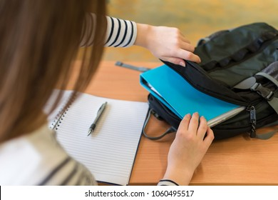 Young female student behind her desk at class, taking out her textbooks from backpack.