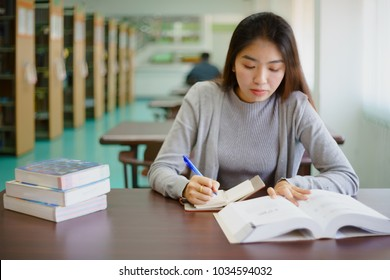Young female student doing self-study  and taking note in university library prepare for her examination. Young woman searching information, taking note, think about her project and assignment.