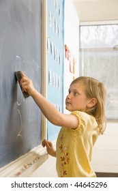 Young female student erasing math problems from blackboard. Vertically framed shot.