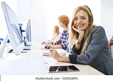 Young female student feeling ready to write exam testing and making individual tasks using technology computer and tablet connected to global network while smiling in university coworking space