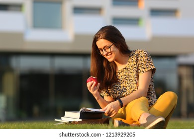 Young female student in glasses with backpack and books sitting on the lawn and eating an apple. Young female have lunch outdoors.