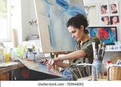 Young female student having classes at art studio, learning how to draw landscapes, trying to mix different watercolors on cardboard. Concentrated woman with dark hair, dressed casually, painting