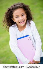 Young female student holding notebooks and looking happy
