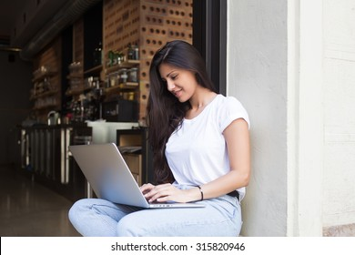 Young female student keyboarding on her laptop computer while sitting in restaurant in the fresh air in summer day ,pretty latin woman connecting to wireless via net-book during morning breakfast