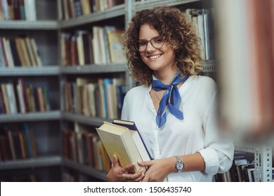 Young female student in the library. Young student holding books.