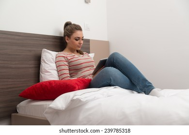 Young Female Student Lying On Bed And Having Fun With Touch Pad In Bedroom