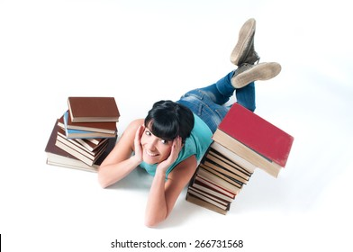 Young female student lying on white between books