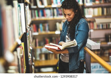 Young female student read and learns by the book shelf at the library.Reading a book.