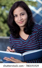 Young female student reading book