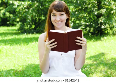 young female student reading a book outdoors