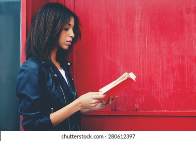 Young female student reading interesting book while standing in the city on red wall background with copy space for your text message, afro american woman read literature while standing outdoors