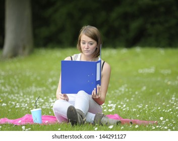 young female student sitting on grass in the  park