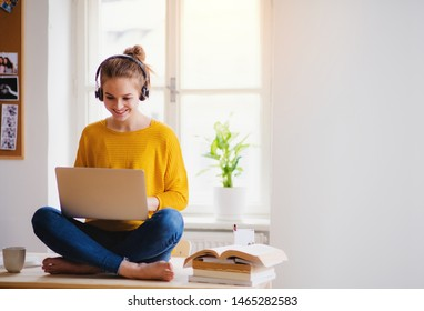 Eine junge Studentin, die am Tisch sitzt und beim Lernen Kopfhörer benutzt.