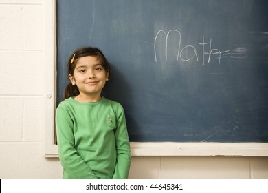 Young female student standing in front of blackboard with 'math' written on it. Horizontally framed shot.