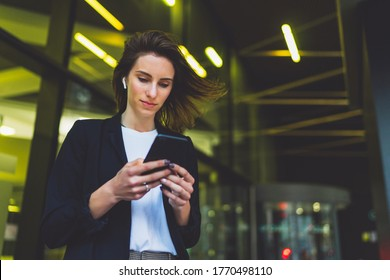 Young female student standing near neon yellow light in night city and listening to music in wireless earphones on modern smartphone. elegant woman watching media video on cellphone device office