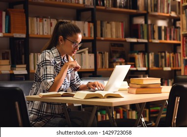 Young female student study in the library using laptop for researching online.