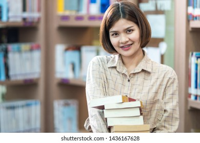 Young female student study in the school library. She is searching for knowledge in the library