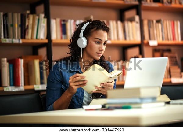 Estudiantes jóvenes estudian en la biblioteca de la escuela. Ella usa laptop y aprende en línea.