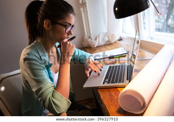 Young female student working at home.She sitting in her working room and doing something on laptop.Look worried .